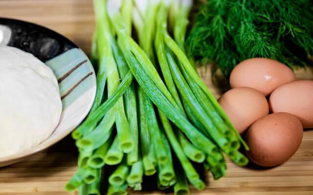 Для приготовления подготовим необходимые для начинки ингредиенты: два пучка зелёного лука, сливочное масло, пучок зелени укропа, четыре куриных яйца, соль и молотый чёрный перец по вкусу. Яйца моем закладываем в кастрюлю, заливаем холодной водо . Добавляем щепотку соли, чтобы яйца не потрескались. Когда вода закипит, уменьшаем огонь, варим яйца вкрутую в течение 10 минут. Сваренные яйца перекладываем в холодную воду, даём остыть.