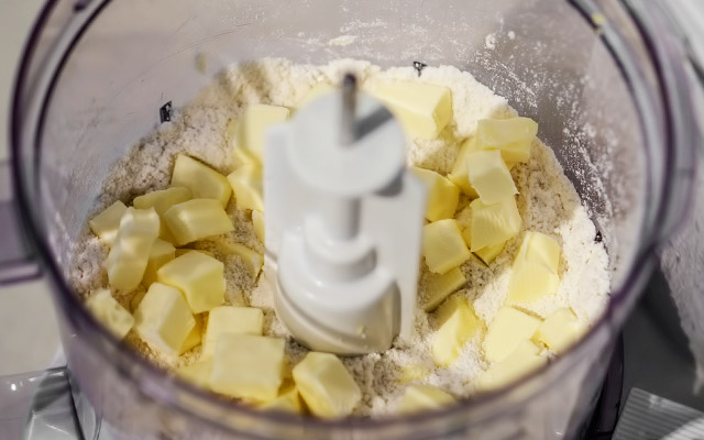 Для приготовления кростаты в чашу кухонного комбайна высыпаем просеянную муку, сахар, щепотку соли и цедру лимона. Смешиваем с помощью комбайна до однородности. Охлаждённое сливочное масло вынимаем из холодильника, нарезаем кусочками и выкладываем к сухим ингредиентам.