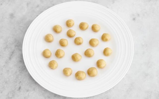 Полученное тесто формируем в шарики. На каждый шарик идёт примерно три четверти чайной ложки теста. Когда большая часть или всё тесто скатано в шарики, разогреваем орешницу на газу. Шарики можно прикрыть пищёвой плёнкой, чтобы не пересохли.