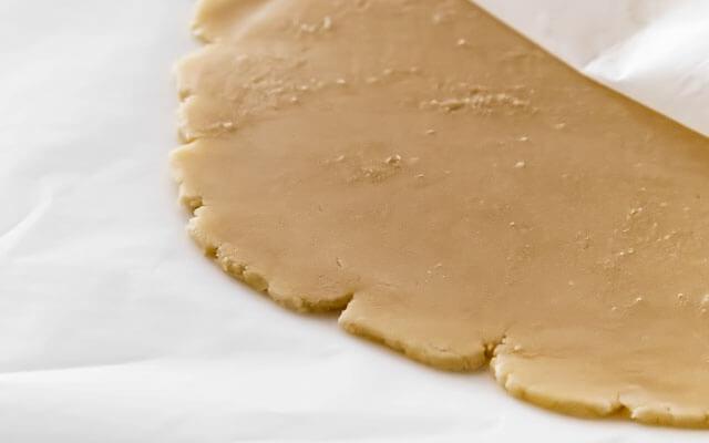 Вынимаем из холодильника и ненадолго оставляем при комнатной температуре, до тех пор, пока тесто на ощупь не станет чуть более пластичным. Чтобы тесто не прилипало к скалке, можно обойтись без присыпания мукой, – раскатываем его между двух слоёв пекарской бумаги. Не надавливаем слишком сильно на края и не истончаем их. Периодически поворачиваем лепёшку, чтобы сохранить её круглую форму.