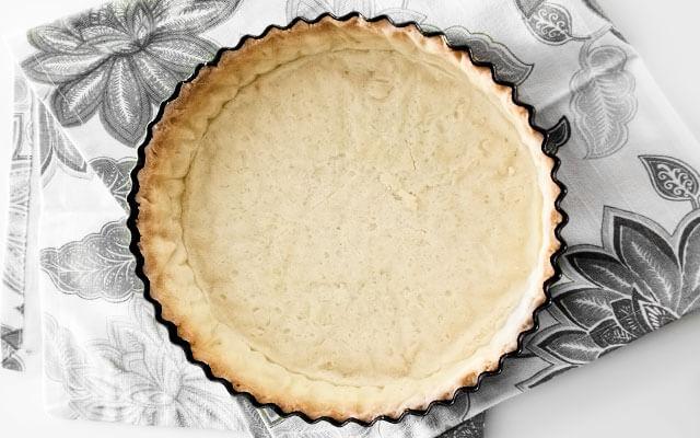 Снимаем пекарскую бумагу и переворачиваем лепёшку в форму для выпечки диаметром 22 см. Формируем бортики и обрезаем излишки. Охлаждаем вместе с формой полчаса в холодильнике. Вынимаем форму, застилаем изнутри бумагой для выпечки, засыпаем фасолью и выпекаем до лёгкой золотистой корочки по краям. Убираем бумагу и фасоль, по необходимости ставим ещё на 5-10 минут в духовку. Заполняем начинкой по своему вкусу.