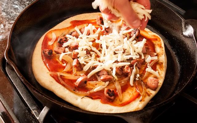 Смазываем несколькими ст.л. соуса, выкладываем начинку и засыпаем тёртым сыром.