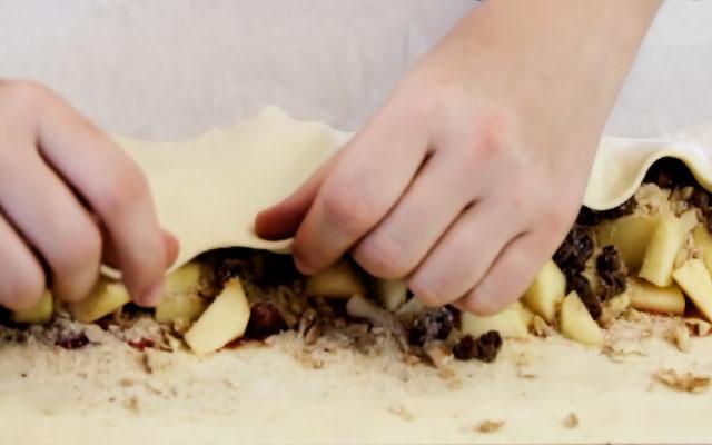 Начинаем заворачивать штрудель. Закрываем начинку свободной третью теста с одной стороны. Отделяем куриный желток от белка. Немного взбиваем желток вилкой и с помощью кулинарной кисточки наносим тонким слоем на свёрнутую часть теста – это поможет скрепить штрудель.