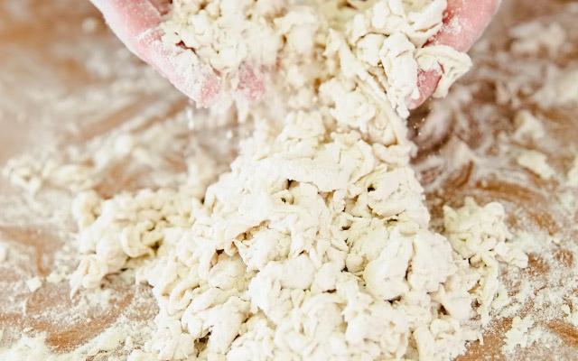 Подготавливаем все необходимые ингредиенты. Высыпаем муку с солью в кучку на рабочую поверхность и делаем углубление в центре. Наливаем в углубление 1 ст.л. ледяной воды и смешиваем муку с водой, распушивая тесто пальцами. Собираем тесто скребком, снова делаем углубление и добавляем ещё 1 ст.л. воды. Продолжаем наливать по 1 ст.л. воды и взбивать пальцами воду с мукой до тех пор, пока они не начнут собираться в большие плотные комки.