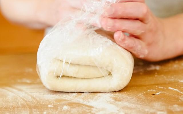 Раскатываем и складываем тесто ещё два раза (всего процедуру нужно повторить 6 раз). На этом шаге тесто должно быть абсолютно гладким на ощупь и очень пластичным. Готовое тесто охлаждаем в пищевой плёнке как минимум 1 час перед выпечкой, а лучше убираем в холодильник на ночь.