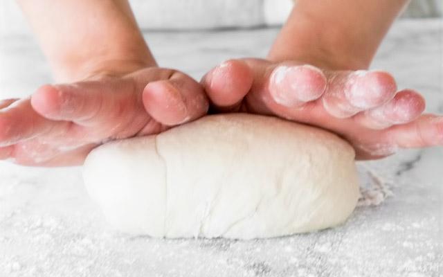 Замешиваем, используя тестомес, или руками на присыпанной мукой разделочной доске в течение 5-8 минут, до тех пор, пока тесто не сформируется в гладкий, слегка липкий шар, пружинящий при нажатии пальцем. Если тесто слишком сильно прилипает к чаше тестомеса или рукам, добавляем ещё немного муки, но не более 1 ст.л. за раз.