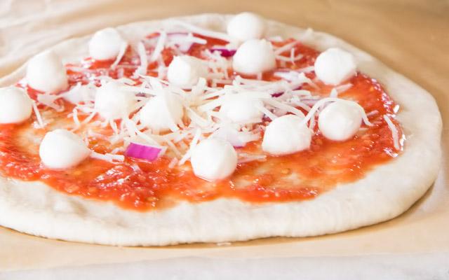 Переносим на пекарскую бумагу, покрываем четвертью стакана соуса, сыром и начинкой по вкусу. Осторожно переносим пиццу на противень или камень и выпекаем до образования золотистой корочки и плавления сыра. Время выпекания зависит от температуры в духовке и того, как тонко или толсто раскатана основа.